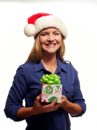 A attractive woman is holding a Christmas gift and smiling Stock Photo