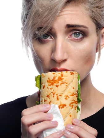 A attractive blonde woman is eating a deli style sandwich