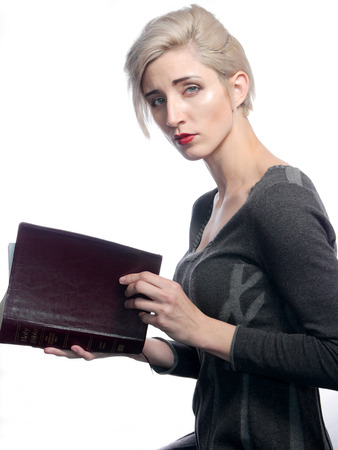 A attractive blond woman is reading a bible