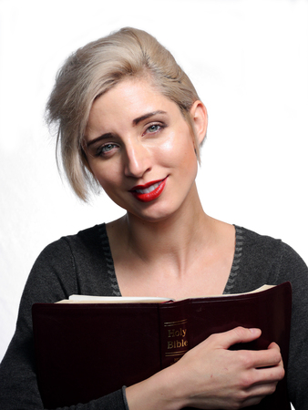 A attractive blond woman is holding a bible and smiling
