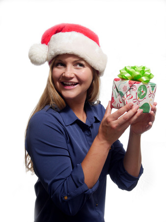A young woman is holding a Christmas gift and wearing a Santa Claus hat