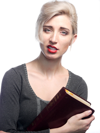 A attractive blond haired woman is holding a bible