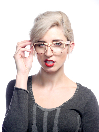 A attractive blonde haired woman is wearing glasses
