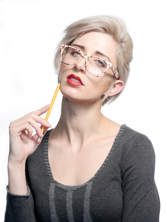 A attractive blonde haired woman is holding a yellow pencil and wearing glasses.