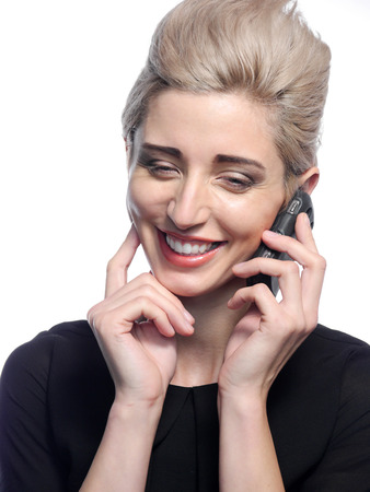 A happy smiling blond haired woman is talking on her cell phone.