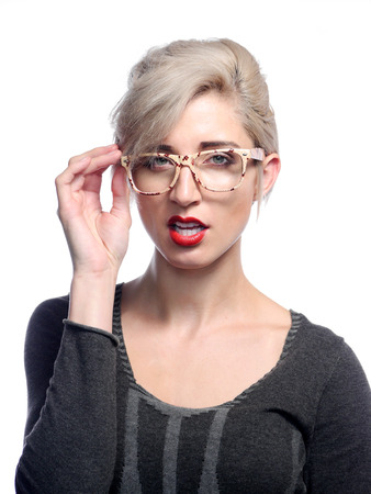 A attractive woman is posing in front of a white background holding a pair of glasses. Stock Photo