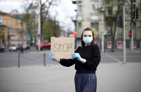 young girl in gloves and a mask holds a banner and shows a protest