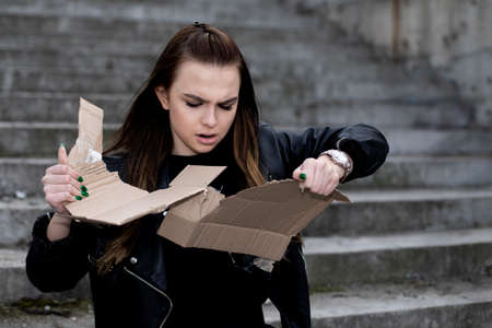 Rebellious girl with long hair in black clothes tearing a cardboard