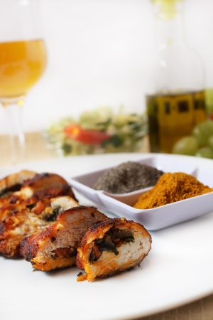 roast chicken breast filled with legume granish, curry, pepper and salad bowls in the background photo