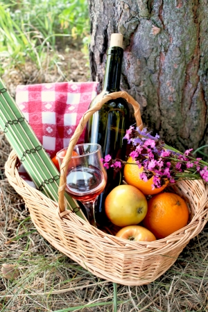 wickery basket for picnic with wine bottle and glass, fruits and field flowers photo