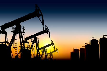 oilfield: silhouettes of oil pumps placed one after another against the sunset  Stock Photo