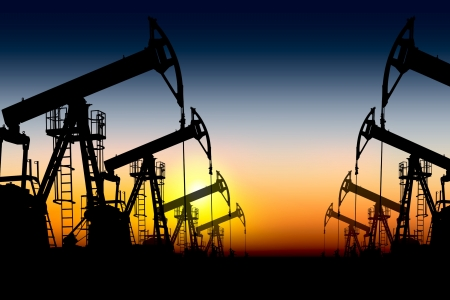 drilling well: silhouettes of oil pumps placed one after another against the sunset  Stock Photo