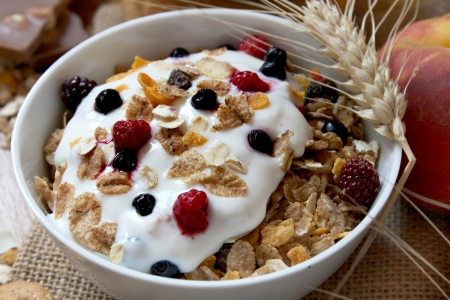 bowl of muesli with raisins and berry fruits, toast and peaches,healthy breakfast rich in fiber Imagens