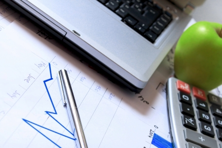 pen over financial chart,laptop,calculator and a green apple,business and economy concept photo