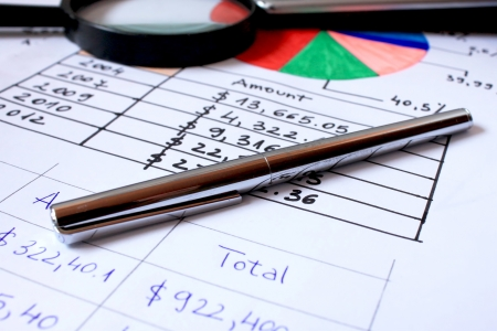 pen placed over financial statistics and charts,business concept photo
