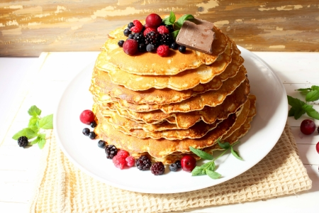 Sweet tasty pancakes with berrie fruits, chocolate and mint leaves photo