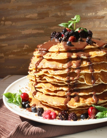 Sweet tasty pancakes with berrie fruits, chocolate syrup and mint leaves photo