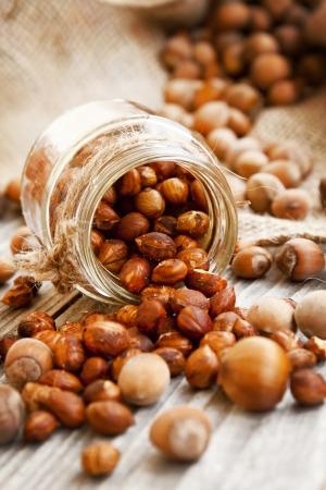 toppled: Roasted Hazelnuts Jar Toppled On Wooden Background