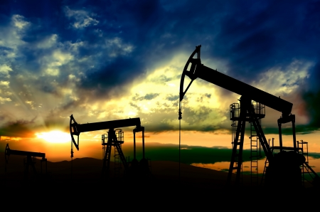 Oil pumps jack.Oil industry equipment working on sunset background