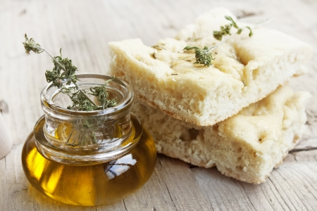 Focaccia italian bread slices with olive oil bottle placed over wooden table Standard-Bild