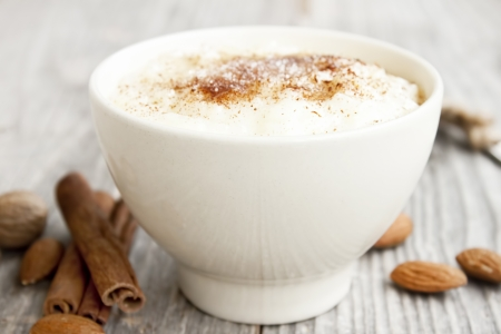 pudding: creamy rice pudding with cinnamon powder,cinnamon sticks and almonds Stock Photo