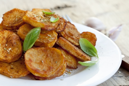 Round spicy baked potatoes with condiments and basil leaves Imagens