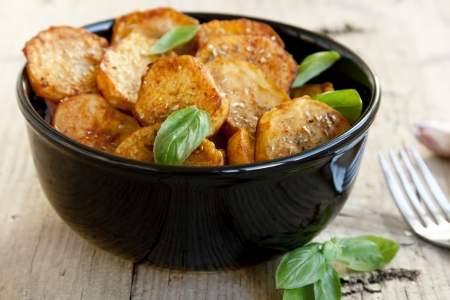 Round spicy baked potatoes with condiments and basil leaves,selective focus Stock Photo