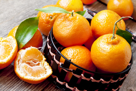 Fresh Clementines in the Basket on Wooden Board with Leaves