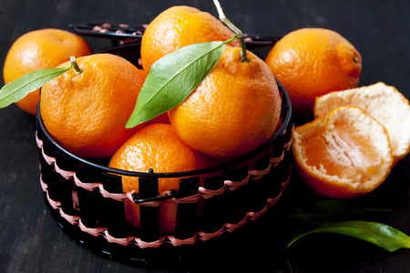 Basket with Fresh Clementines, Sweet Orange Fruits with Leaves photo
