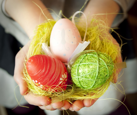 Child Hands Holding Colorful Easter Eggs with Artificial Grass photo