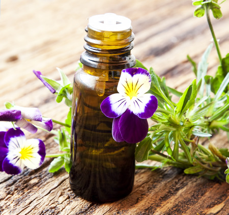 Pansy Essential Oil Bottle with Bright Violet Flowers on Wooden Background Imagens