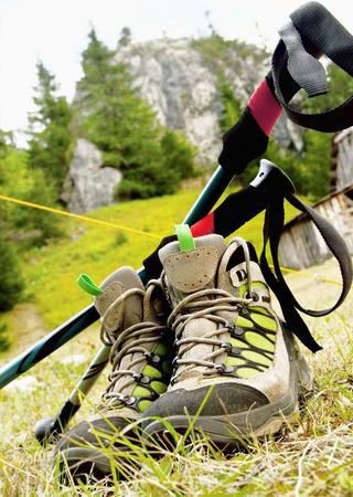 Berg wandelschoenen en wandelstokken op Outdoor Achtergrond met rotsen en bomen Stockfoto