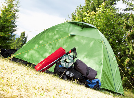 sleeping pad: Mountain Camping Equipment with a Tent, Backpack, Trekking Poles and Sleeping Pad Stock Photo
