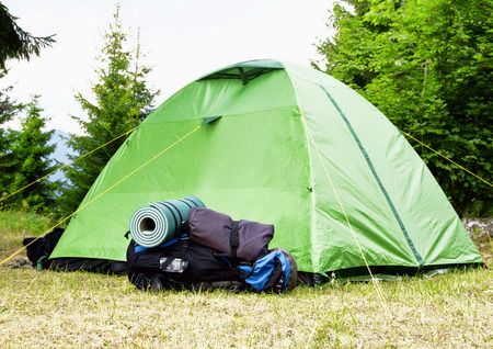 sleeping pad: Mountain Camping Equipment with a Tent, Backpack and Sleeping Pad Stock Photo