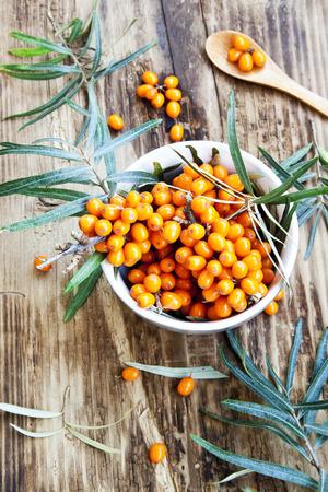 argousier: Argousier baies dans un bol avec des feuilles sur fond de bois