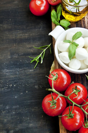 Verse mediterrane ingrediënten, mozzarella, basilicum, olijfolie, tomaten en kruiden voor Italiaanse Koken Recept op houten tafel Stockfoto