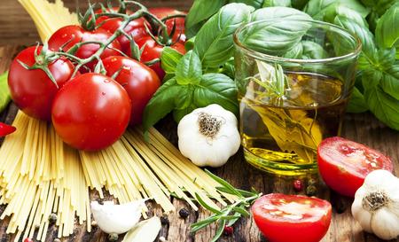 신선한 지중해 재료, 체리 토마토, 마늘, 바 질, 이탈리아 스파게티, 목조 배경에 올리브 오일