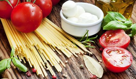 Mediterranean Ingredients, Cherry Tomatoes, Garlic,Spices, Italian Spaghetti,Olive Oil on Wooden Background photo