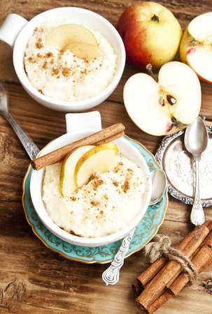 Rice Pudding with Apple Slices and Cinnamon Spice Sticks on Wooden Background Imagens