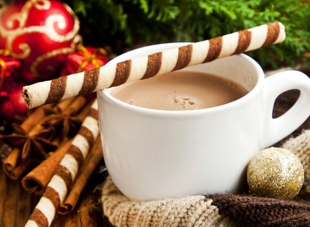 Hot Chocolate Cup with Spiral Snacks and Christmas Decoration in the Background