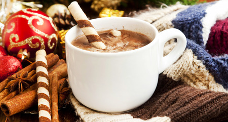 Hot Chocolate Cup with Spiral Snacks and Christmas Decoration in the Background photo
