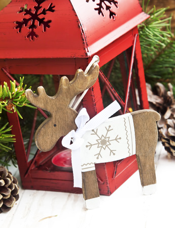 Vintage Wooden Reindeer Christmas Decoration on Christmas Lantern and Fir Tree Branches photo