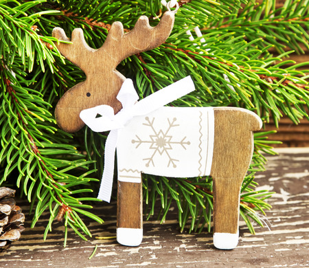 Vintage Wooden Reindeer Christmas Decoration and Green Fir Tree Branches photo