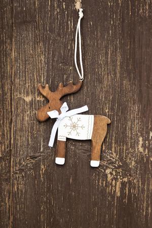 Vintage Wooden Reindeer Christmas Decoration on Old Wooden Background photo