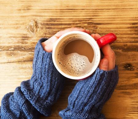 Warme handen met chocolade beker op houten achtergrond