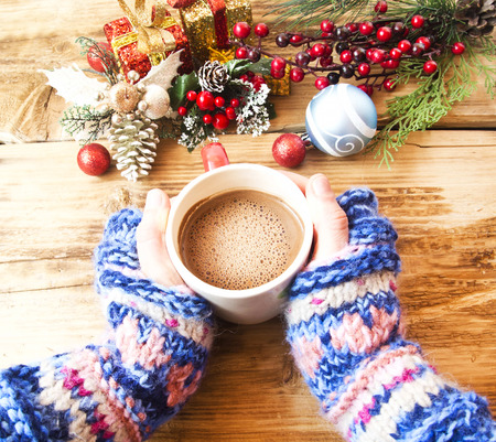 Warm Hands Holding Chocolate Cup with Christmas Decorations Imagens