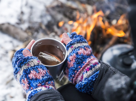 Hands Holding Hot Tea Cup Outdoor near Fire Place photo