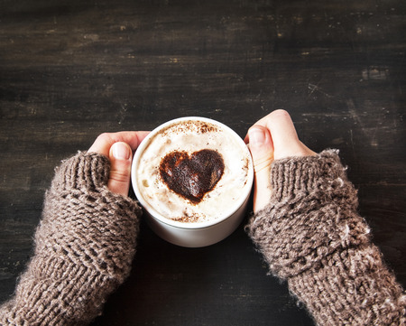 colores calidos: Hands Holding Warm Cappuccino with Froth and Cocoa Heart Shape Foto de archivo