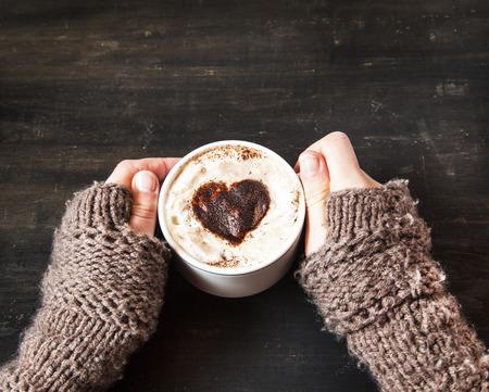 corazon humano: Manos que sostienen Cappuccino caliente con espuma y cacao en forma de coraz�n