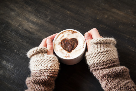 Hands Holding Warm Cappuccino with Froth and Cocoa Heart Shape Imagens